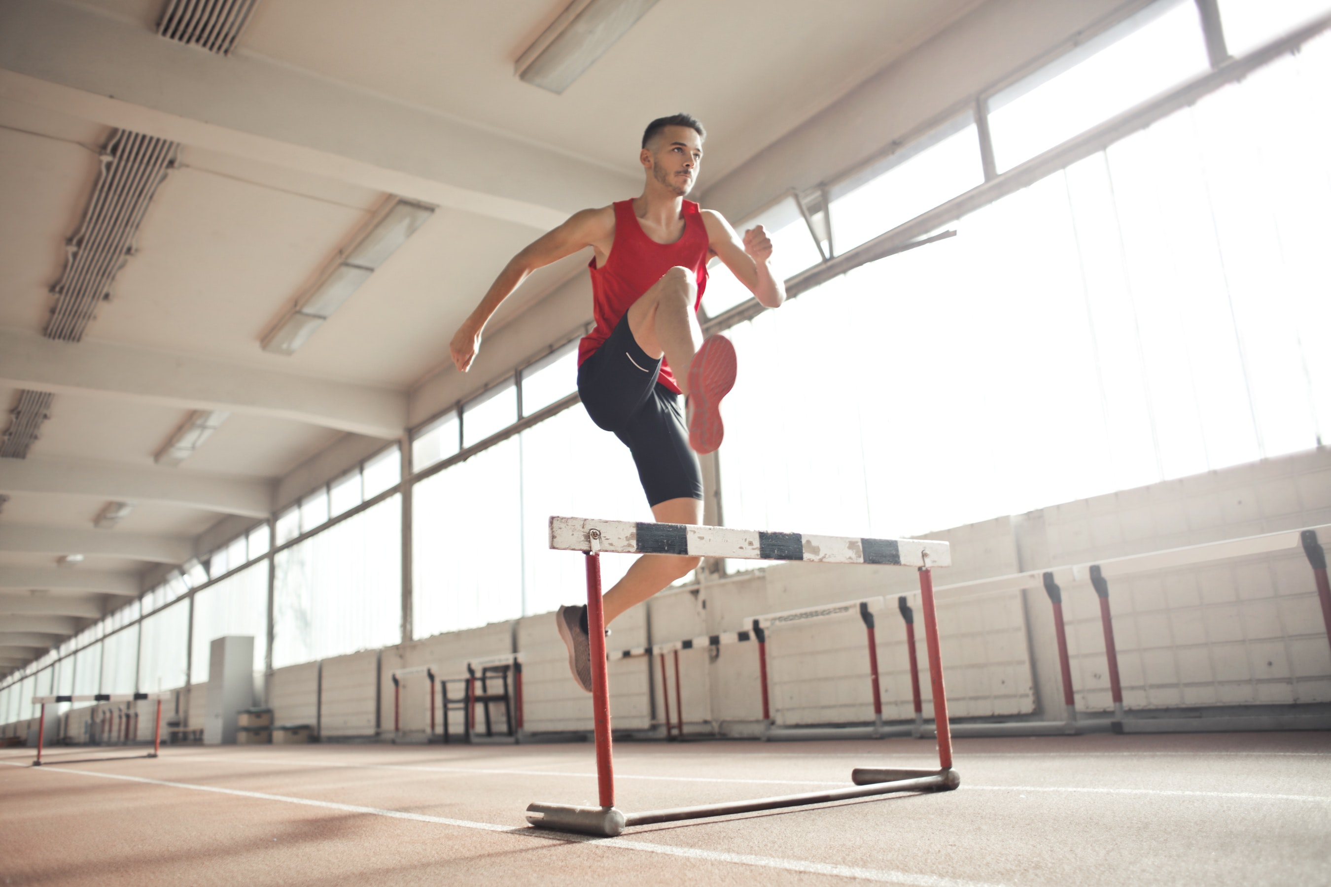 athlete jumping over a bar